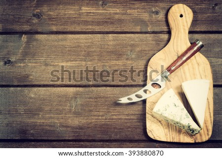 Cheese with white mold it and stainless steel cheese knife with wood handle are is lying on the board of olive wood. All is lying on the wooden desk. Photo is edited as an vintage with dark edges.  - stock photo