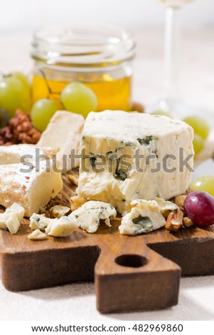 cheeseboard, fruits and honey on white table, closeup