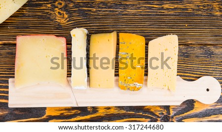 Cheeseboard with assorted cheeses arranged on a buffet table in a neat row on a rustic wooden table at a catered event - stock photo