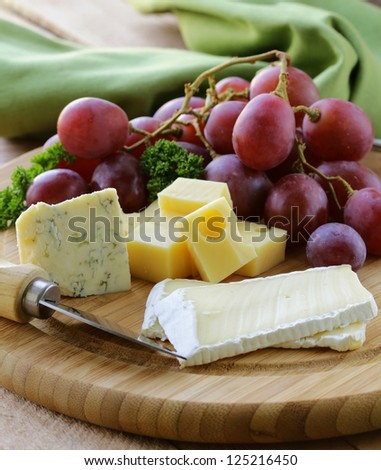 cheeseboard with three kinds of cheese and grapes - stock photo