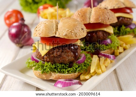 Cheeseburger and french fries on the table.Selective focus on the front burger - stock photo