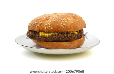 Cheeseburger and Mustard in sesame seeded bun isolated in plate on white from overhead.  - stock photo