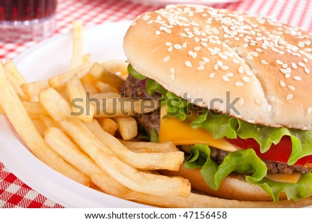 cheeseburger, french fries and cola on a plastic plate - stock photo