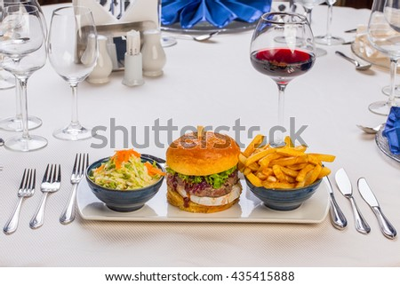 cheeseburger, fried potatoes and salad on a classy restaurant table
