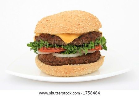 Cheeseburger in a bun, over white, with lettuce salad, tomato, onion, close up, macro