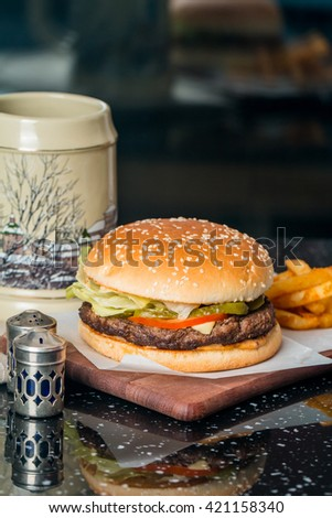 Cheeseburger on sesame buns with succulent beef patties and fresh salad ingredients on paper served  with French Fries and Beer on black table - stock photo