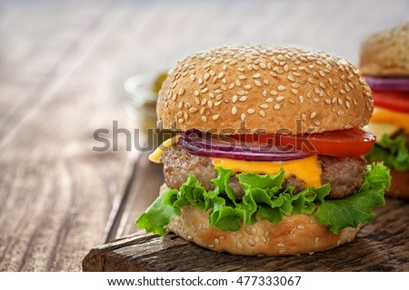 Cheeseburger on wooden table with copy space