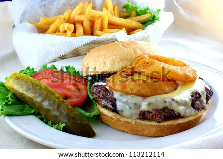 Cheeseburger topped with onion rings with fries - stock photo