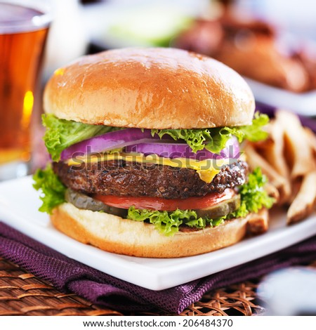 cheeseburger with beer and french fries close up - stock photo