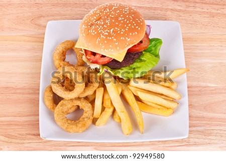 Cheeseburger with chips and onion rings on the plate - stock photo