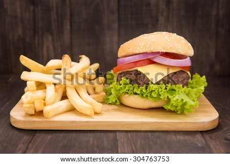 Cheeseburger with french fries on wooden background.