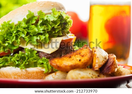 Cheeseburger with fried potatoes on a plate with beer glass - stock photo