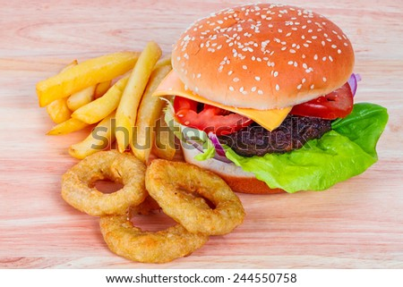 Cheeseburger with lettuce, tomato and onion rings - stock photo