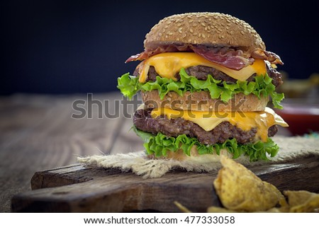 Cheeseburger with potato and beer on wooden table