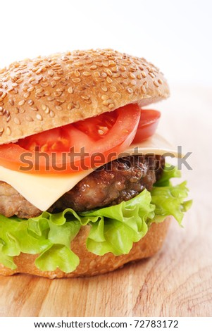 Cheeseburger with tomatoes and lettuce on a wooden table - stock photo