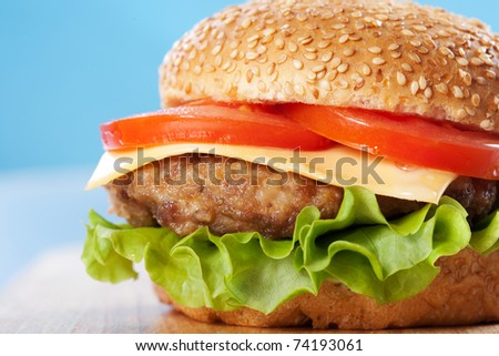 Cheeseburger with tomatoes and lettuce on a wooden table with blue background - stock photo