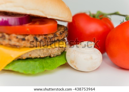 Cheeseburger with tomatoes and mushroom on a white background.