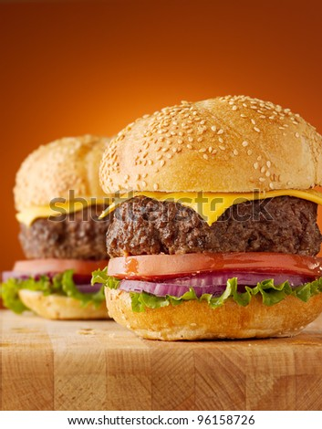 cheeseburgers on wooden board with an orange vignetted background.