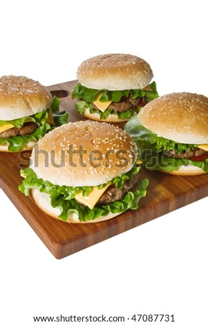 Cheeseburgers on wooden cutting board isolated on white.