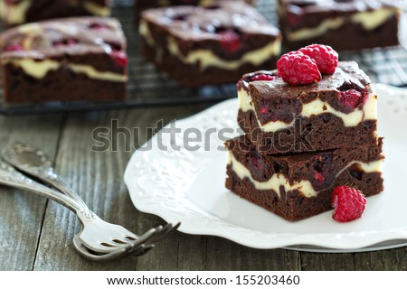 Cheesecake brownies with raspberry stacked on a plate - stock photo