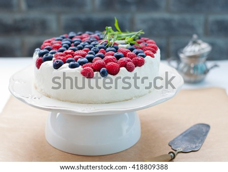 Cheesecake, cream mousse cake with fresh berries on a white plate Grey stone background. Selective focus - stock photo