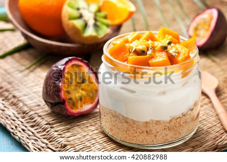 cheesecake in a jar  with tropical fruits: mango, passionfruit, kiwi slices, orange and passionfruit on straw background - stock photo