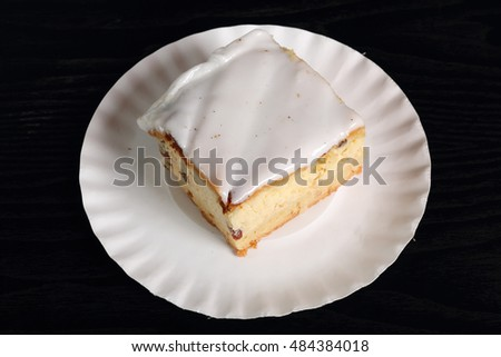 Cheesecake on disposable paper plate. Cheesecake with raisins topped with sugar icing.