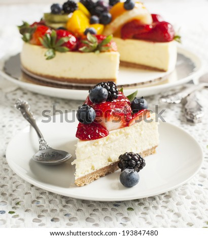 Cheesecake topped with fresh berries and fruits - stock photo