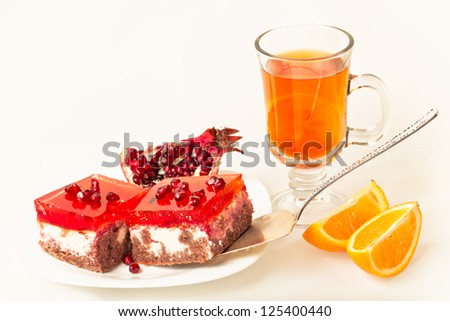 Cheesecake with a cup of tea orange slices and pomegranate - stock photo
