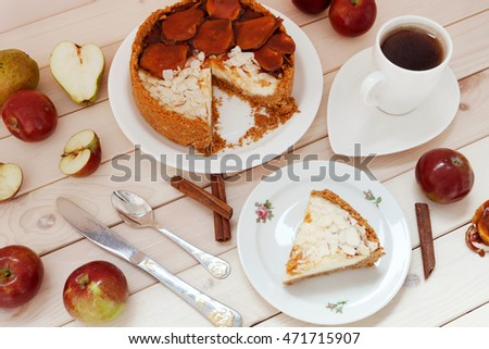 Cheesecake with caramel and cup of tea on wooden background.