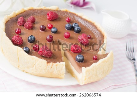 Cheesecake with chocolate layer decorated with blueberries, raspberries and cranberries on white plate on pink napkin. Slice cut out, close up image in bright morning - stock photo