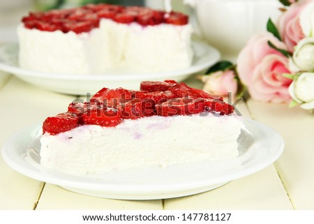 Cheesecake with fresh strawberry on white plate on wooden table