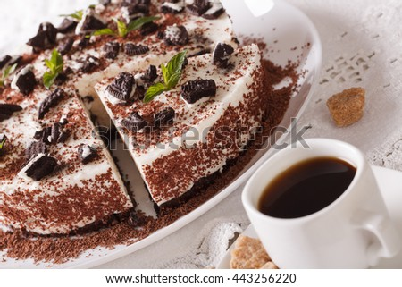 cheesecake with pieces of chocolate cookies and coffee close-up on the table. horizontal