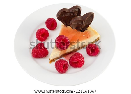 cheesecake with raspberries and chocolate hearts on the plate on white background