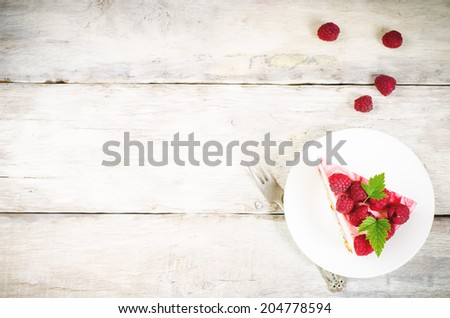 cheesecake with raspberries on a white wood background. toning. selective focus on leaves - stock photo