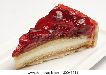 Cheesecake with strawberry topping on a white plate - stock photo