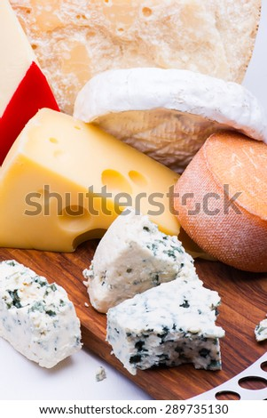 Cheeses on chopping board on white background - stock photo