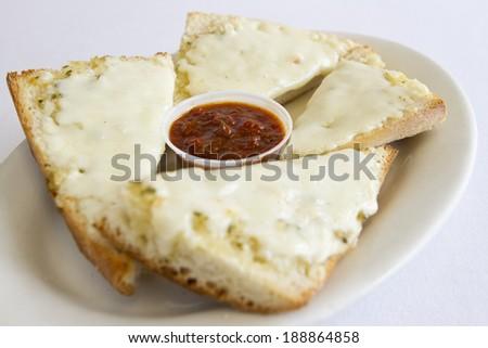 Cheesy bread on a plate with marinara. - stock photo