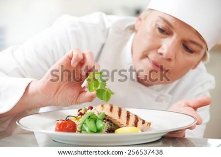 Chef Adding Garnish To Meal In Restaurant Kitchen - stock photo