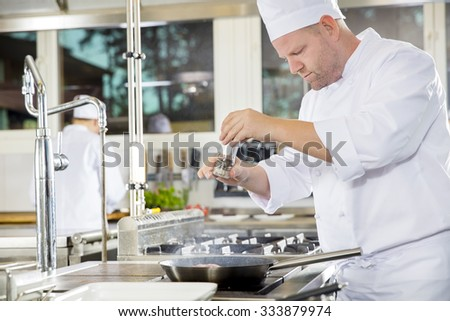 Chef adding pepper on steak in a professional kitchen - stock photo
