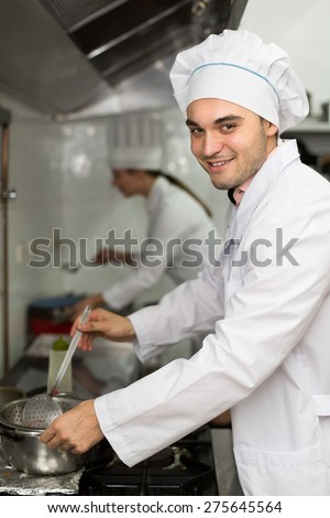 Chef and his assistant preparing meal in restaurant. Focus on man - stock photo