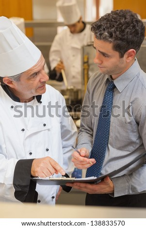 Chef and waiter having a discussion in the kitchen - stock photo