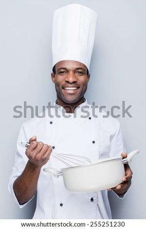 Chef at work. Cheerful young African chef in white uniform mixing something in casserole while standing against grey background - stock photo