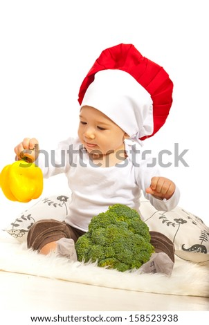 Chef baby holding bell pepper and broccoli against white background - stock photo