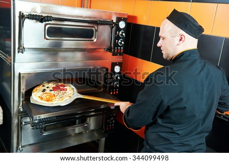 chef baker cook in black uniform putting pizza into the oven with shovel at restaurant kitchen - stock photo