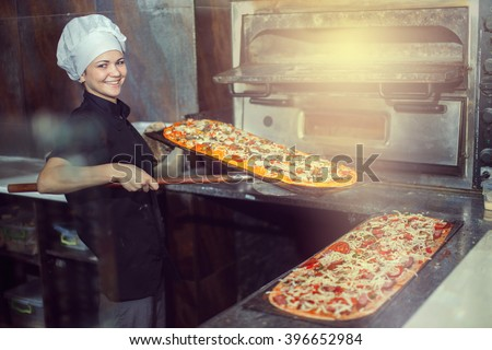 chef baker cook in black uniform putting pizza into the oven with shovel at restaurant kitchen