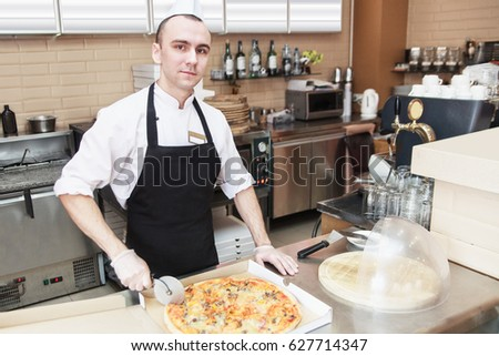 Chef baker in uniform cutting pizza at kitchen.