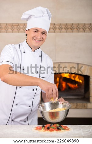 Chef baker is imposing cheese to pizza. - stock photo