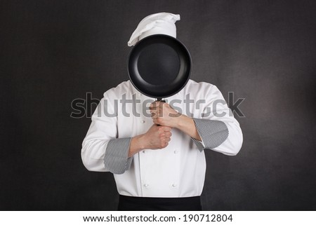 Chef behind pan black background - stock photo