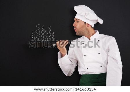 Chef blowing smoke from pan  - stock photo